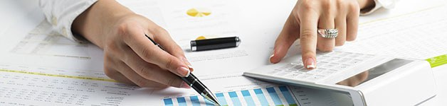 A foto mostra as duas mãos de uma pessoa, sendo que na direita ela está segurando uma caneta e escrevendo em um papel e na esquerda, utilizando uma calculadora.